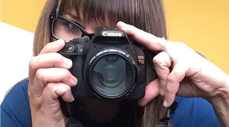 A woman pointing a DSLR camera. Only one eye is visible above the camera.